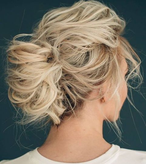 a curly and super messy updo for medium hair with a messy bump and bangs