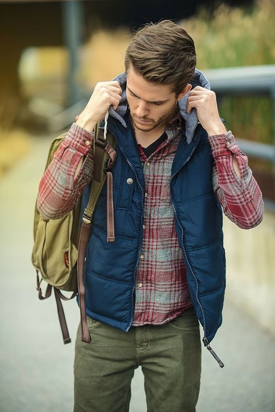 a dynamic winter outfit with green pants, a black tee, a plaid shirt, a navy waistcoat with a hood and backpack