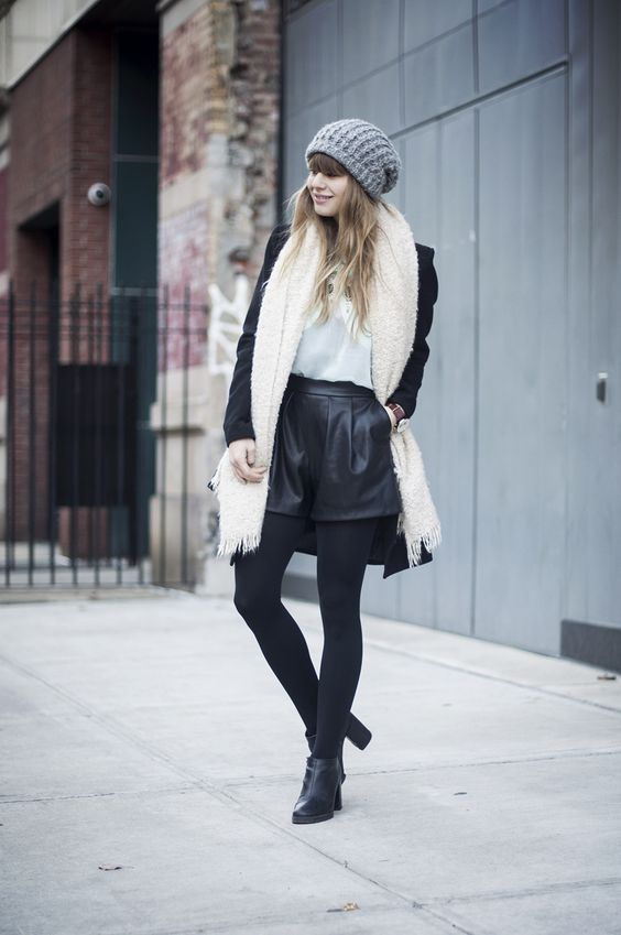 black tights, booties, leather shorts, a printed tee, a black coat, a creamy fluffy scarf and a grey beanie
