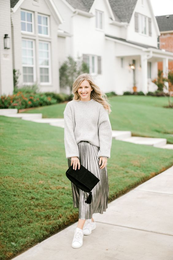a grey cashmere oversized sweater, a grey pleated metallic midi skirt, white sneakers and a black suede clutch