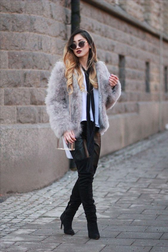 a white blouse with a black tie, black leather pants, tall black boots and a grey fur coat