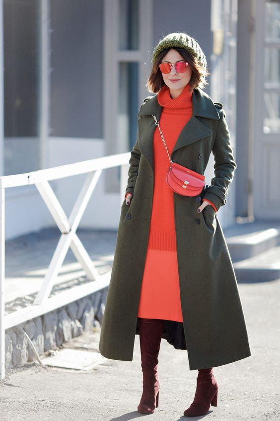 a coral turleneck sweater, a coral midi skirt, brown boots, a dark green midi coat, a dark green beanie