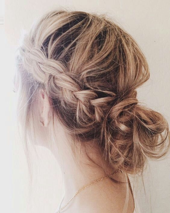 a messy low bun with two side braids is an effortlessly chic option for Christmas parties