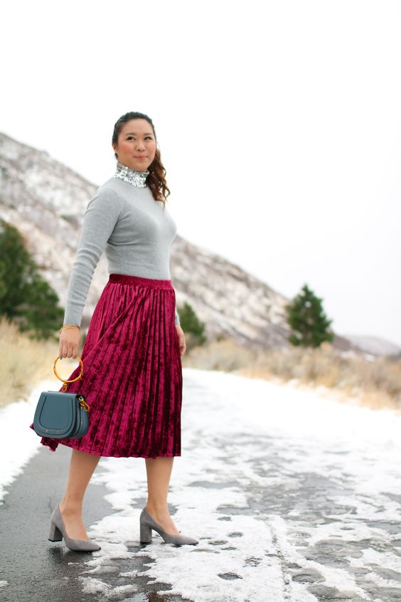 a plum-colored pleated velvet midi skirt, a grewy sweater with a sequined high neckline, grey shoes and a small bag