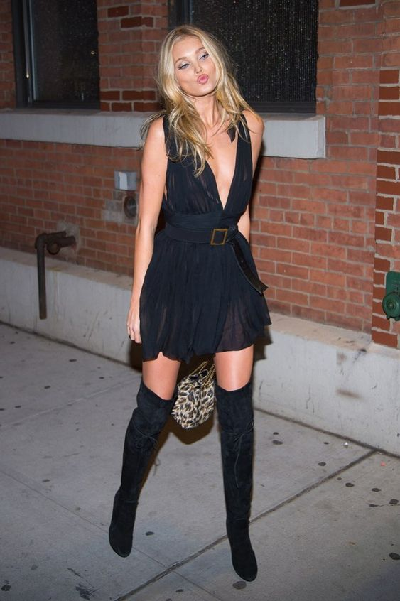 a black partly sheer mini dress with a plunging neckline, tall suede boots and a clutch