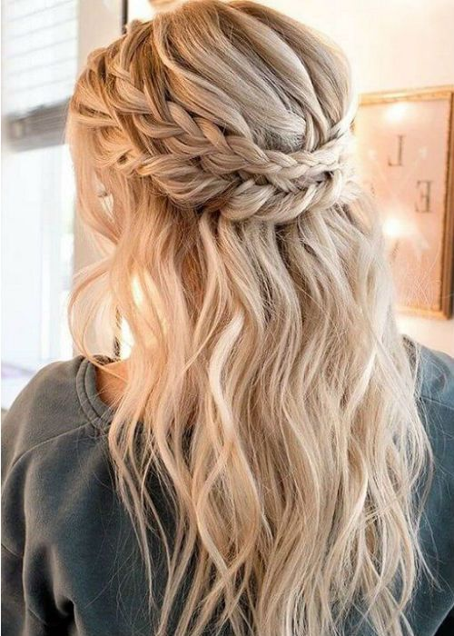 a romantic half updo with a double braided halo and waves plus bangs for parties