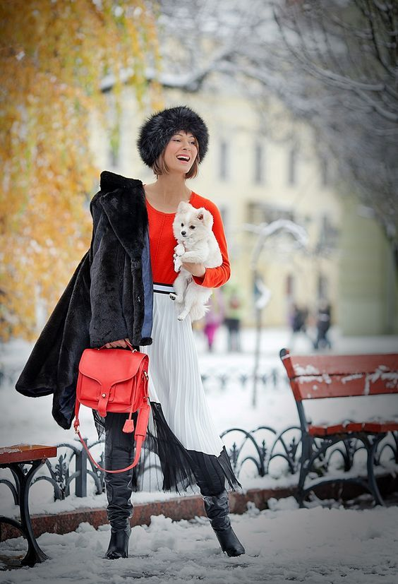 an orange sweater, a white and black pleated skirt, a black fur coat, black boots and a coral bag