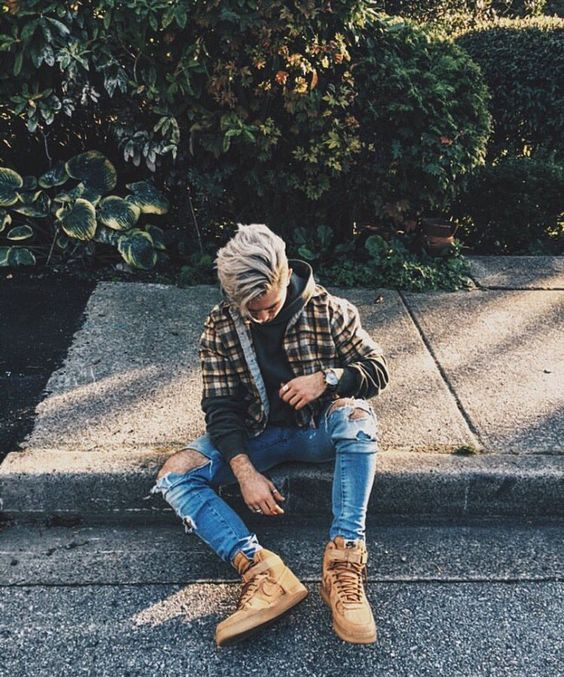 blue ripped jeans, a green hoodie, a plaid shirt, tall tan boots create a relaxed winter outfit