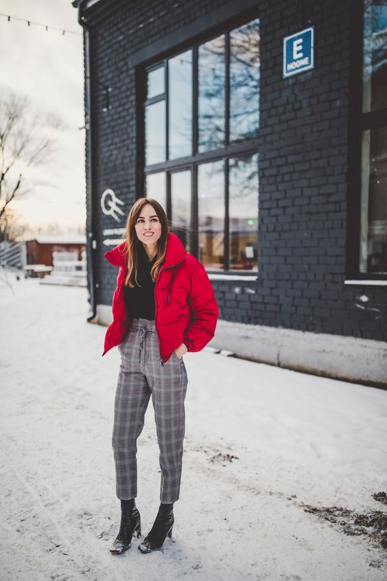 a black sweater, high waist grey plaid pants, black boots and a red puffer jacket