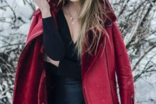 06 a black top with a V-neckline, a black leather skirt and a deep red shearlign coat for a colorful touch
