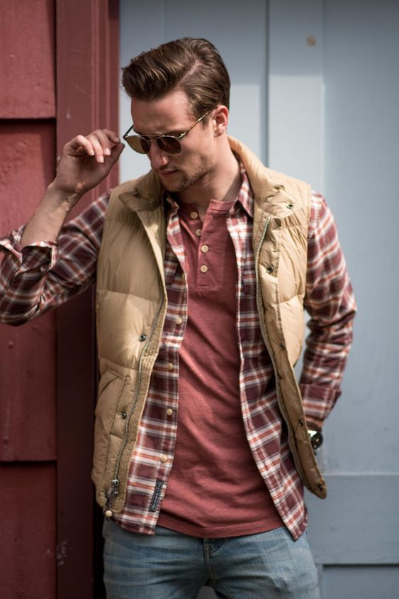 a layered casual look with a tree, a plaid shirt, a tan puffer vest and blue jeans for fall or winter
