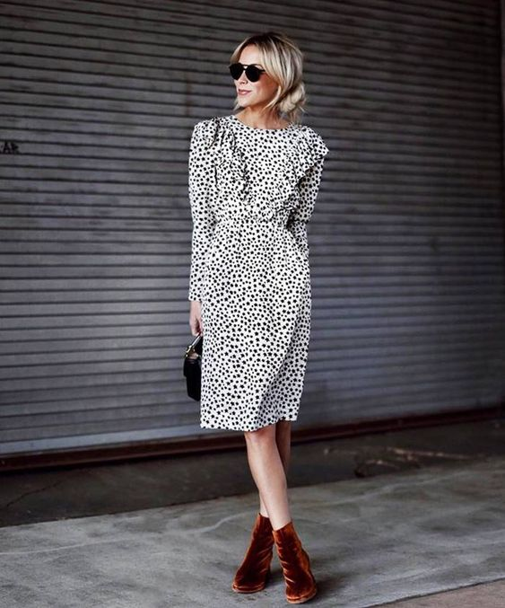 a printed knee dress with a ruffled bodice, a black bag and rust-colored velvet booties