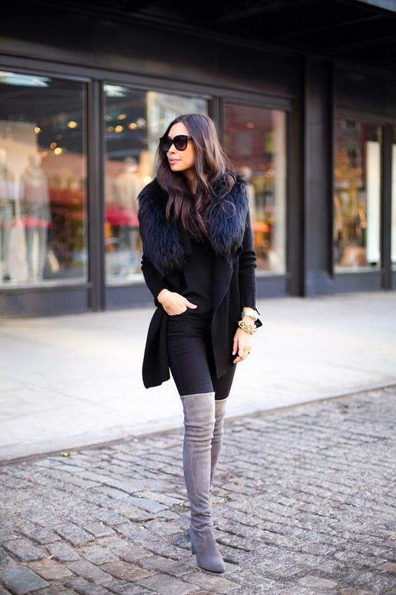 black skinnies, a black sweater, tal grey boots, a black coat with fur a sexy and sleek look