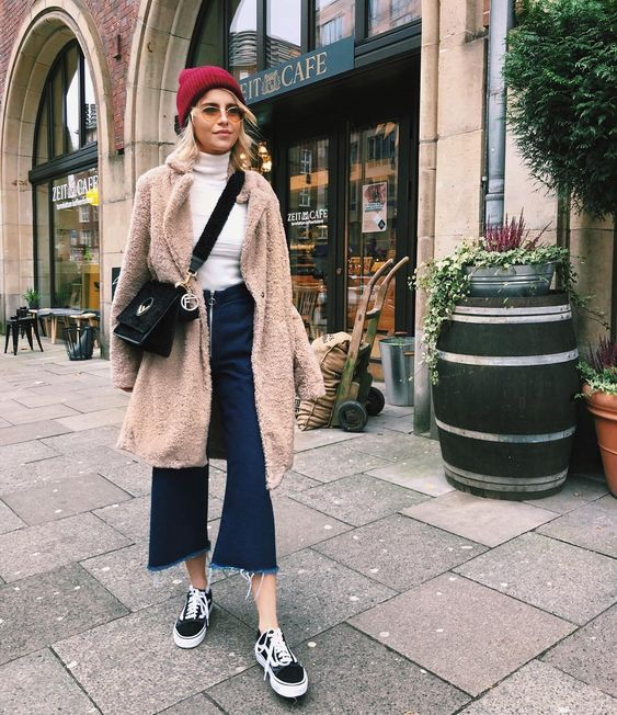 navy cropped jeans, a white turtleneck, black sneakers, a camel teddy coat and a red beanie
