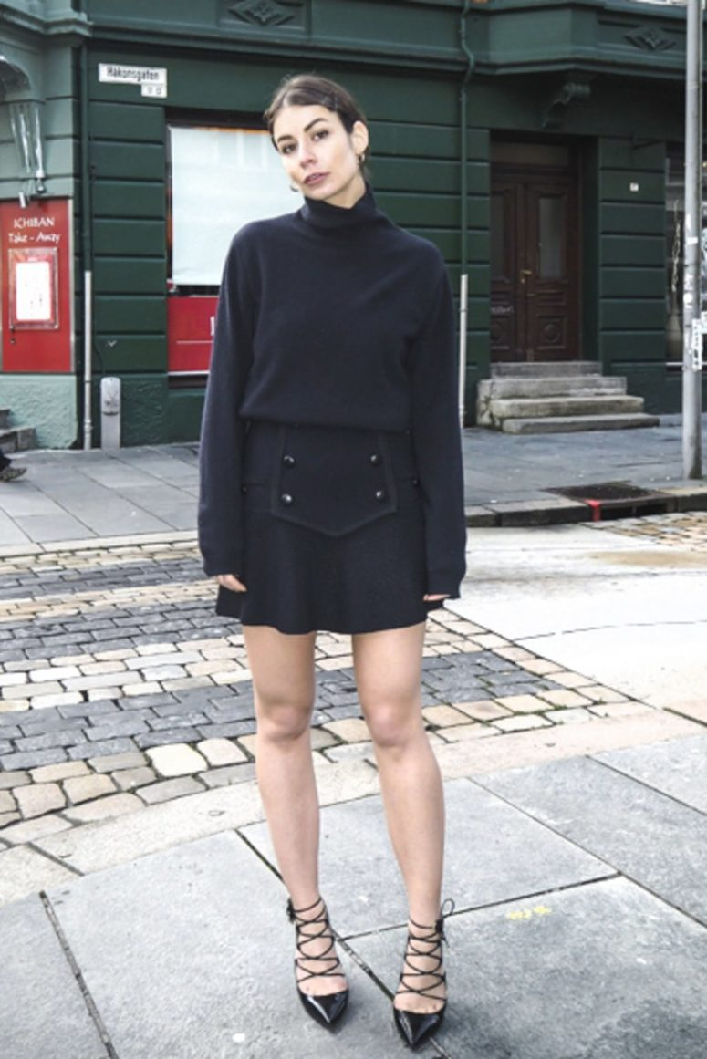 a black turtleneck, a black mini skirt with buttons and black lace up shoes make up a monochromatic look
