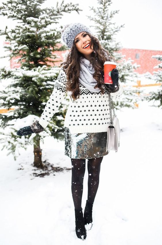 a printed sweater, a silver sequin short skirt, black tights, black booties, a grey beanie and mittens