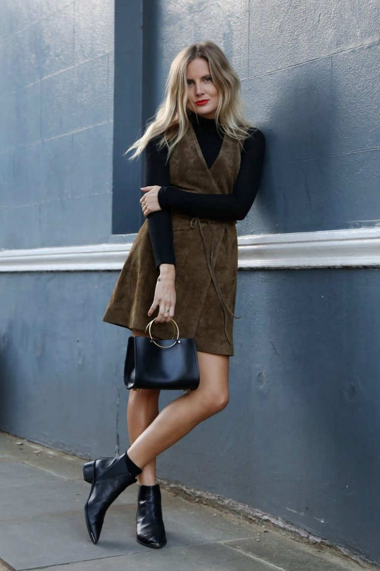 a black turtleneck, a brown suede dress, a black bag and black booties to rock