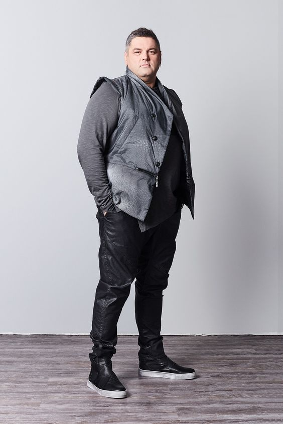 a grey long sleeve top, a quilted vest, black leather pants, black leather boots for a rock inspired look