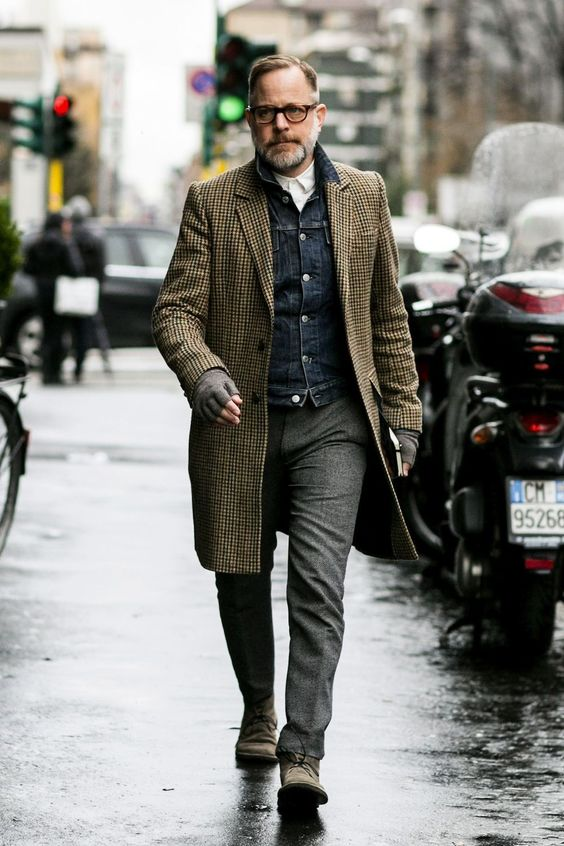 a relaxed everyday look with a white shirt, a denim jacket, grey pants, grey shoes and a retro-printed overcoat