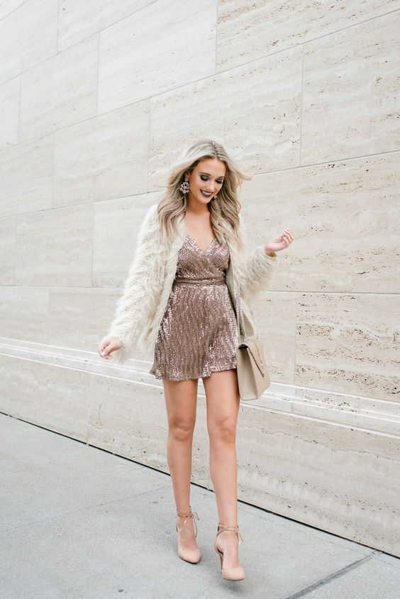 a rose gold sequin mini dress, nude shoes with lacing, a neutral fur coat and a nude bag plus a dark lip