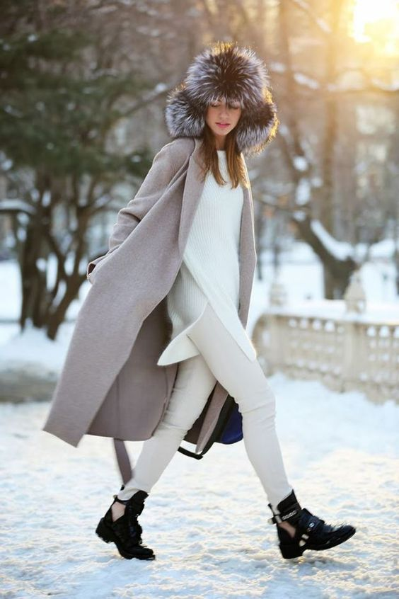 a white long sweater, white jeans, black cutout boots, a neutral midi coat and a large fur hat