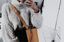 08 black jeans, an oversized cable knit turtleneck sweater, a camel bucket bag for a stylish outfit