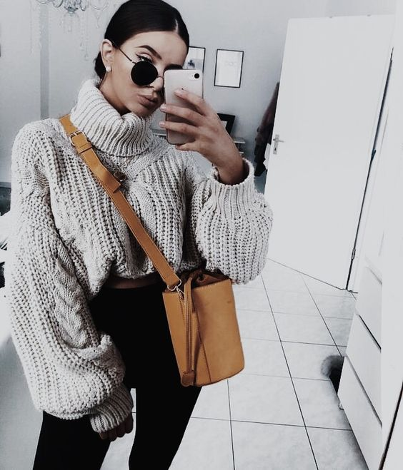 black jeans, an oversized cable knit turtleneck sweater, a camel bucket bag for a stylish outfit