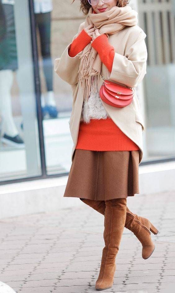 a coral oversized sweater, a brown midi skirt, brown tall boots, a camel coat and a matching scarf, a coral bag