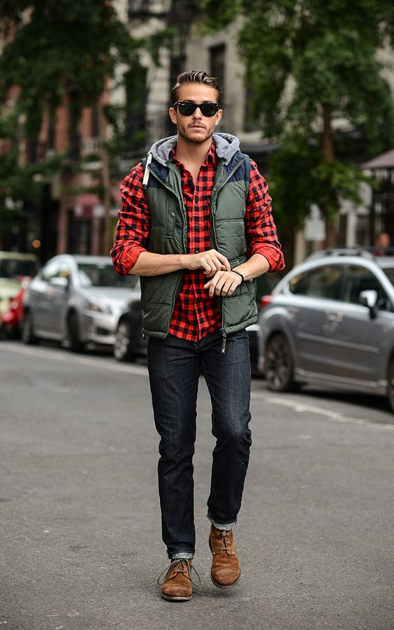 a plaid shirt, black jeans, amber shoes, an olive green vest and sunglasses for a comfy holiday look