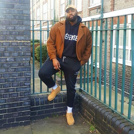 a sporty look with a black hoodie, black sport pants, yellow moccasins, a brown coat and a cap