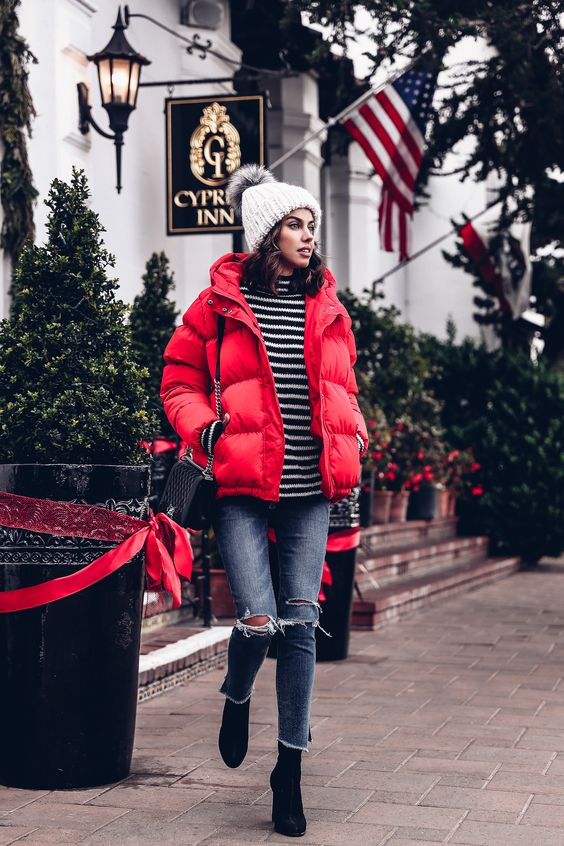 a striped turtleneck, ripped blue skinnies, a red puffer jacket, black boots, a grey beanie