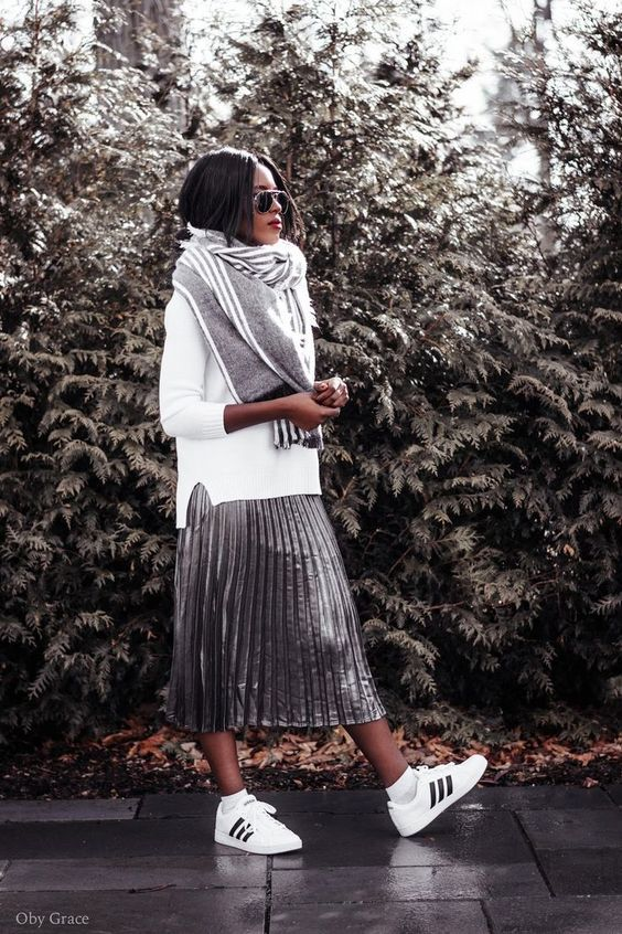 a white sweater, a grey striped scarf, a metallic pleated midi skirt, white sneakers for a sporty touch