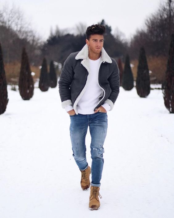 blue ripped jeans, camel boots, a white sweater and a grey and white shearling jacket