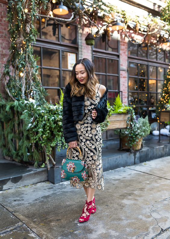 a black and gold sequin slip dress, lace up shoes, a green printed bag and a fur cropped jacket