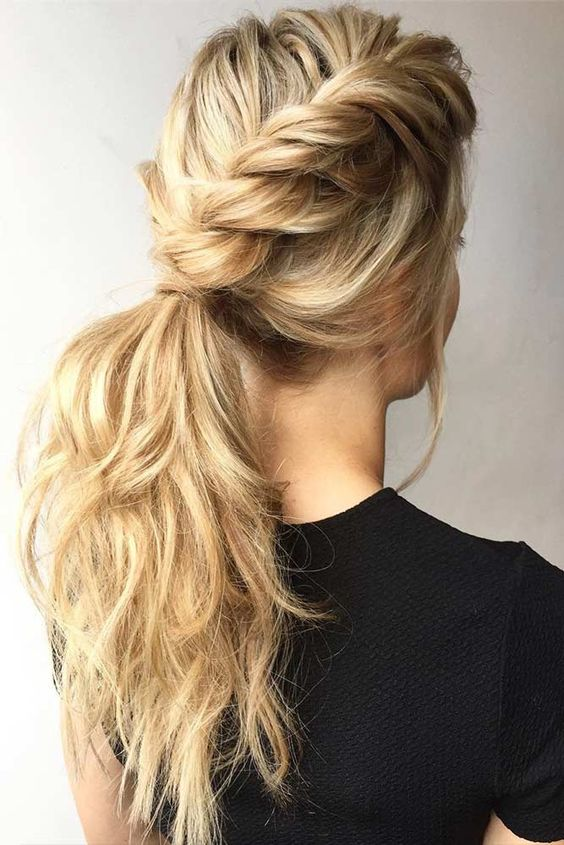 a low ponytail made of two twisted side braids, with waves and a bump plus bangs
