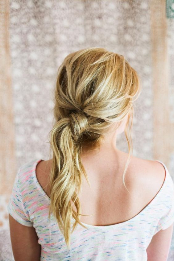 a messy and textural low side ponytail with some bangs and a bump is a fast DIY hairdo