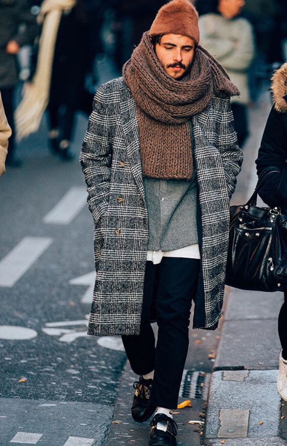 a comfy layered look with a grey shirt, black jeans, black shoes, a grey plaid coat and an oversized brown scarf