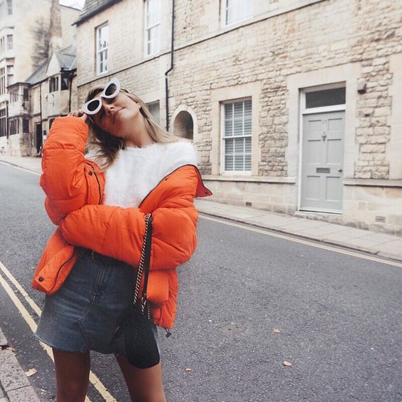 a fun and fresh look with a fuzzy white sweater, a denim mini and an orange puffer coat