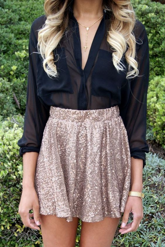 a gold sequin mini with a high waist and a black sheet blouse with long sleeves and a V neckline