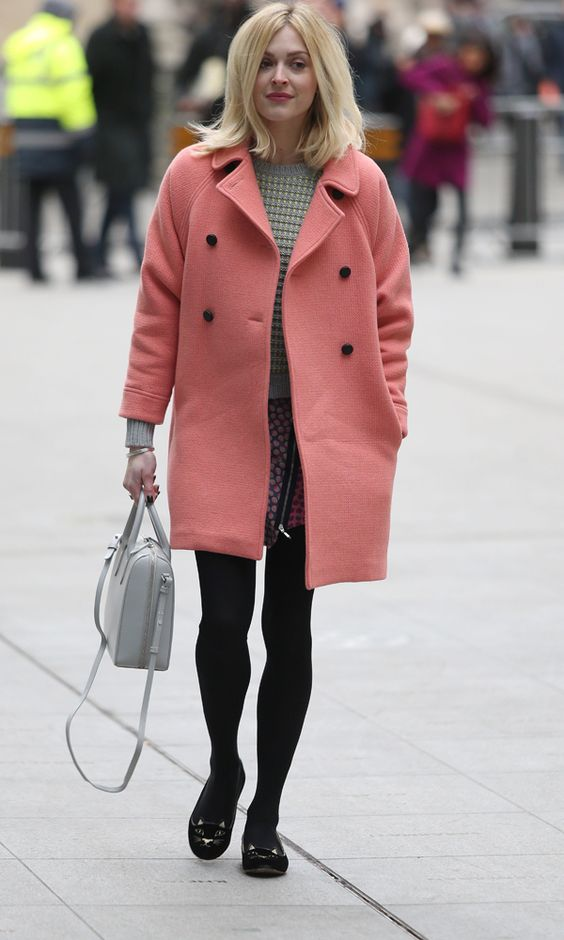 a green sweater, a wrap skirt, black tights and kitty flats, a grey bag and a soft coral coat