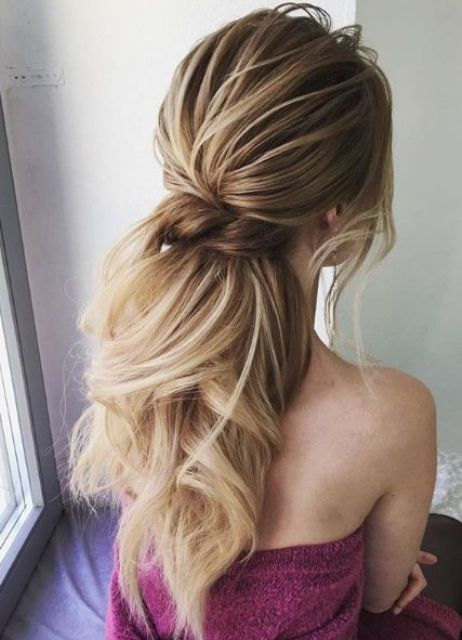 a low twisted ponytail with waves, a bump and bangs is a gorgeous idea to show off your hair