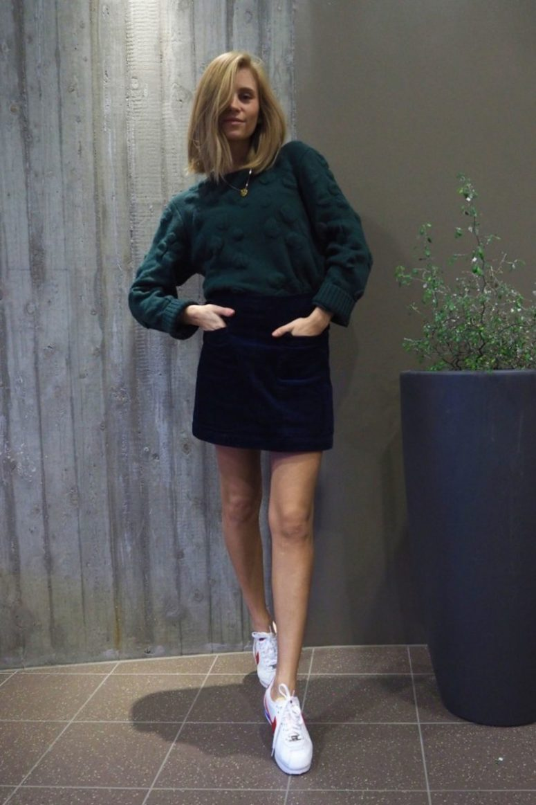 a navy velvet mini skirt with pockets, a forest green sweater, white sneakers for a casual look