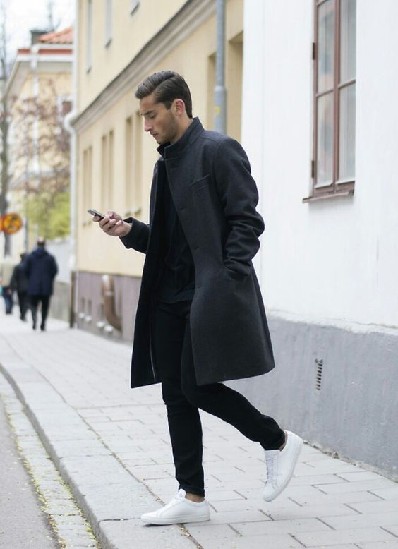 a total black look with jeans, a top, an overcoat is refreshed with white sneakers