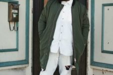 11 a white shirt, ripped jeans, green sneakers and a matching long bomber jacket plus a cap