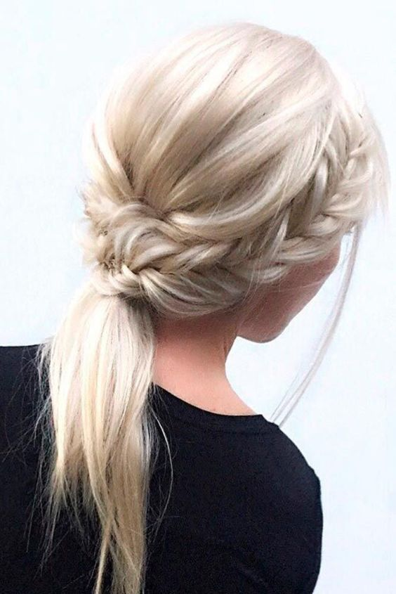 a low ponytail with two side fishtail braids and a bump is a chic and casual option
