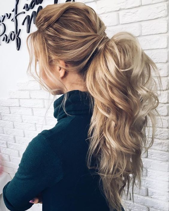a luxurious messy and wavy ponytail with bangs and a large bump is a bold idea for long hair