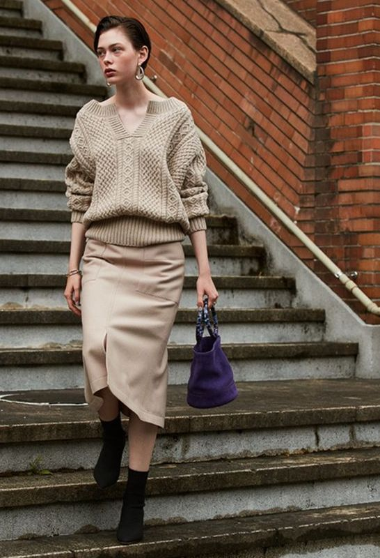 a neutral off the shoulder sweater, a neutral midi skirt, black sock boots and a purple bag