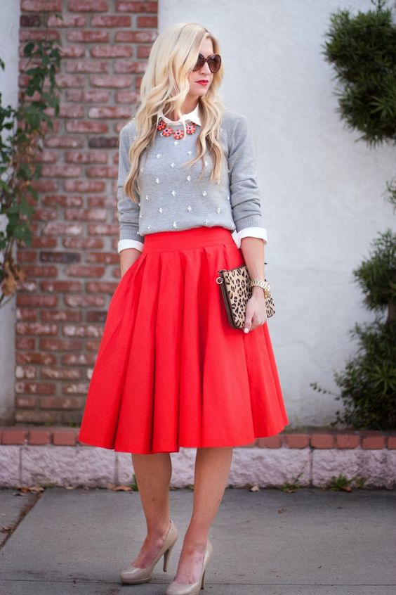 a pleated hot coral midi skirt, an embellished sweater, a statement necklace, nude heels and a leopard clutch