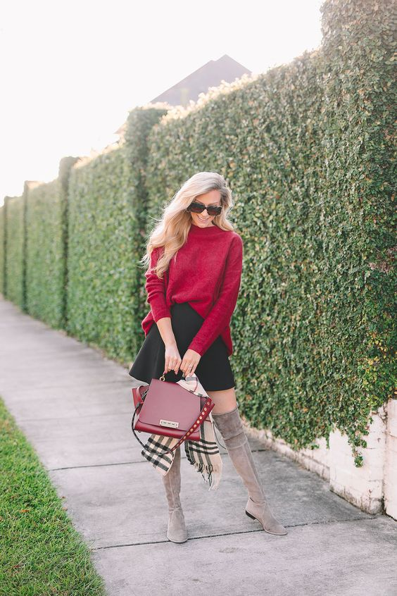 a red oversized sweater, a black A-line mini, grey tall boots and a red bag for a playful touch