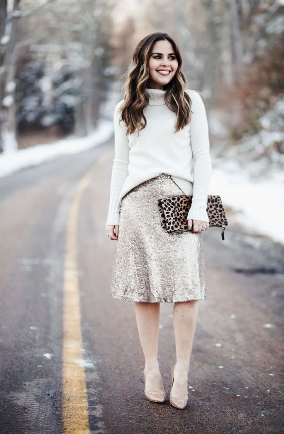 a white turtleneck sweater, a silver sequin A line skirt, nude shoes and a leopard printed clutch